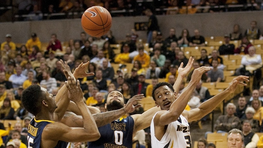 West Virginia's Terry Henderson, left, Remi Dibo, center, and Missouri's Johnathan Williams III, right, battle for a rebound during the first half of an NCAA college basketball game Thursday, Dec. 5, 2013, in Columbia, Mo. (AP Photo/L.G. Patterson)