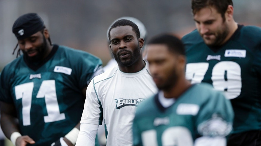 Philadelphia Eagles quarterback Michael Vick, center, and teammates walk off the field after practice at the NFL football team's training facility, Thursday, Dec. 5, 2013, in Philadelphia. (AP Photo/Matt Rourke)