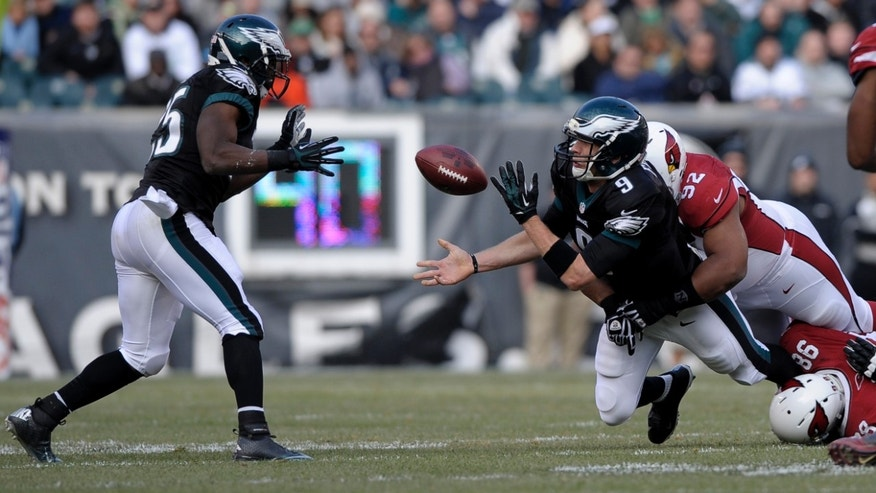 Philadelphia Eagles' Nick Foles (9) tosses to LeSean McCoy (25) as he is tackled by Arizona Cardinals' Dan Williams (92) and Frostee Rucker (98) during the first half of an NFL football game on Sunday, Dec. 1, 2013, in Philadelphia. (AP Photo/Michael Perez)