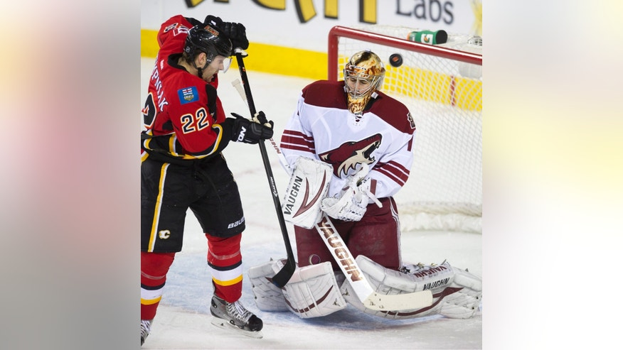 Phoenix Coyotes' goalie Thomas Greiss, right, from Germany, makes a save as Calgary Flames' Lee Stempniak looks for a rebound  during the first period of an NHL hockey game, Wednesday, Dec. 4, 2013 in Calgary, Alberta.  (AP Photo/The Canadian Press, Larry MacDougal)