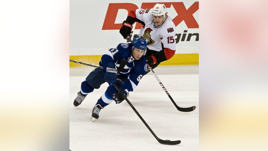 Tampa Bay Lightning's Valtteri Flippula (51) clears the puck from Ottawa Senators' Zack Smith (15) during the second period of an NHL hockey game on Thursday, Dec. 5, 2013, in Tampa, Fla. (AP Photo/Steve Nesius)