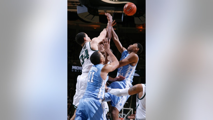 North Carolina's Brice Johnson (11) and Isaiah Hicks, right, and Michigan State's Gavin Schilling (34) and Adreian Payne, center, fight for a rebound during the second half of an NCAA college basketball game, Wednesday, Dec. 4, 2013, in East Lansing, Mich. North Carolina won 79-65. (AP Photo/Al Goldis)