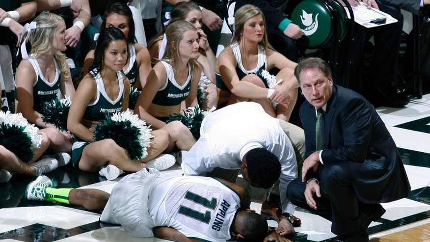 Michigan State coach Tom Izzo, right, and trainer Quinton Sawyer, center, tend to Keith Appling (11) after he went down with an injury during the first half of an NCAA college basketball game against North Carolina, Wednesday, Dec. 4, 2013, in East Lansing, Mich. (AP Photo/Al Goldis)