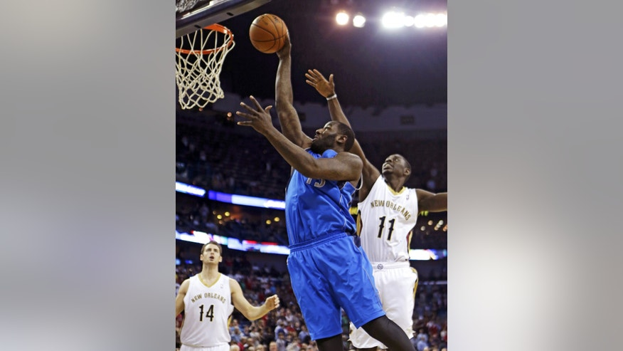 Dallas Mavericks center DeJuan Blair (45) drives to the basket between New Orleans Pelicans point guard Jrue Holiday (11) and center Jason Smith (14) in the first half of an NBA basketball game in New Orleans, Wednesday, Dec. 4, 2013. (AP Photo/Gerald Herbert)