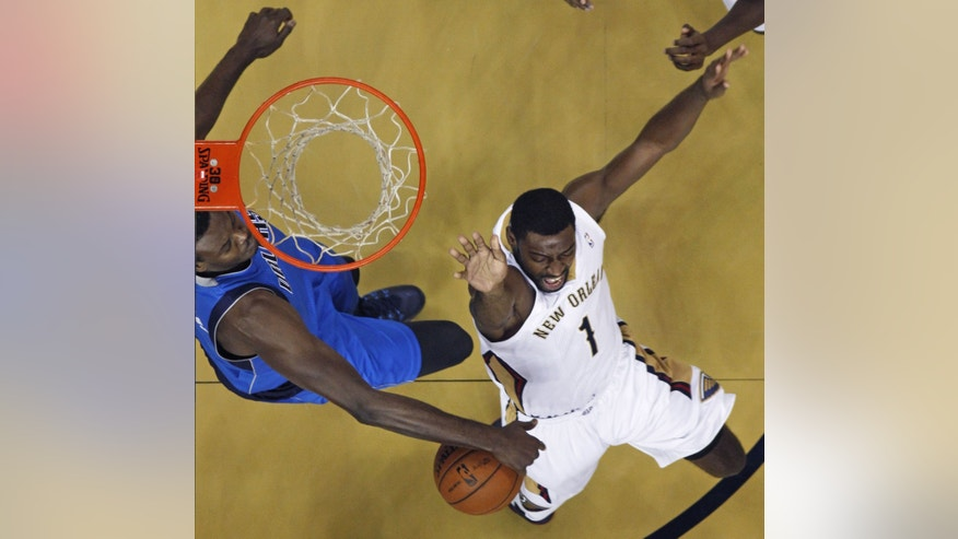 New Orleans Pelicans point guard Tyreke Evans (1) is stripped of the ball by Dallas Mavericks center Samuel Dalembert, left, as he drives to the basket in the first half of an NBA basketball game in New Orleans, Wednesday, Dec. 4, 2013. (AP Photo/Gerald Herbert)