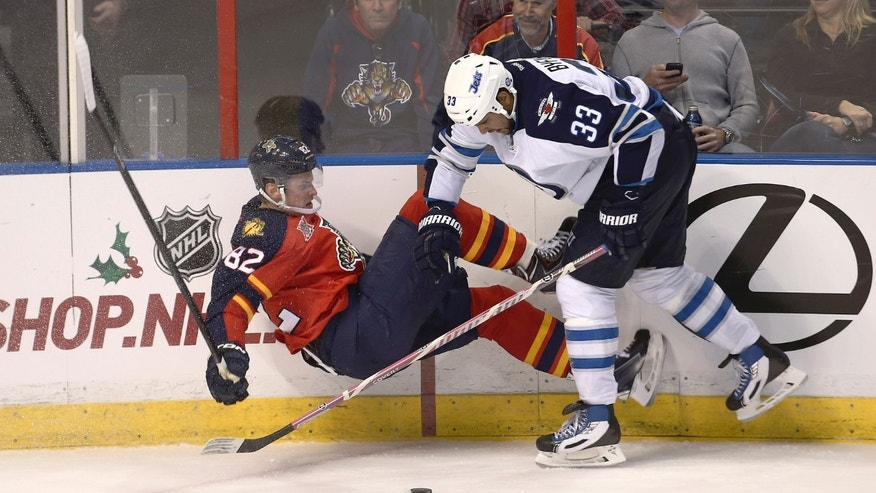 Winnipeg Jets' Dustin Byfugilen (33) knocks Florida Panthers' Tomas Kopecky (33) to the ice during the third period of a NHL hockey game in Sunrise, Fla., Thursday, Dec. 5, 2013. The Panthers won 5-2. (AP Photo/J Pat Carter)