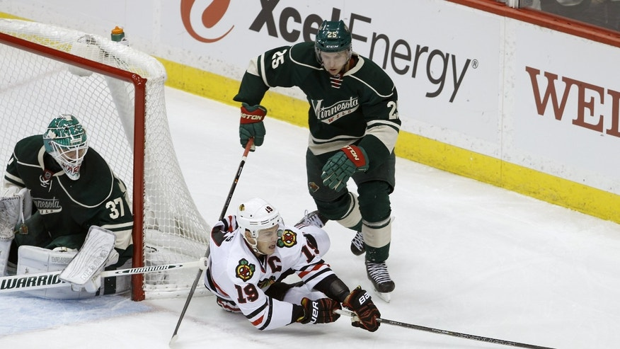Chicago Blackhawks center Jonathan Toews (19) and Minnesota Wild defenseman Jonas Brodin (25) chase the puck as Minnesota Wild goalie Josh Harding (37) covers the net during the first period of an NHL hockey game in St. Paul, Minn., Thursday, Dec. 5, 2013. (AP Photo/Ann Heisenfelt)