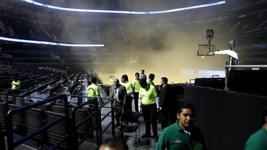 December 4, 2013: People leave as smoke engulfs the basketball court before a regular season NBA game between the Minnesota Timberwolves and the San Antonio Spurs in Mexico City. NBA spokeswoman Sharon Lima says the smoke was coming from a generator fire outside the arena. (AP Photo)