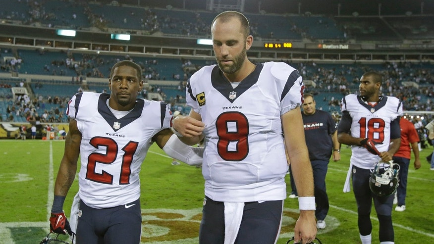 Houston Texans cornerback Brice McCain (21) pats quarterback Matt Schaub (8) on the back as they walk off the field with wide receiver Lestar Jean (18) after losing to the Jacksonville Jaguars 27-20 in an NFL football game in Jacksonville, Fla., Thursday, Dec. 5, 2013.(AP Photo/John Raoux)