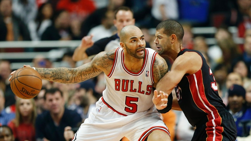 Chicago Bulls forward Carlos Boozer, left, looks for an opening against Miami Heat forward Shane Battier, right, during the first half of an NBA basketball game in Chicago, Thursday, Dec. 5, 2013. (AP Photo/Kamil Krzaczynski)