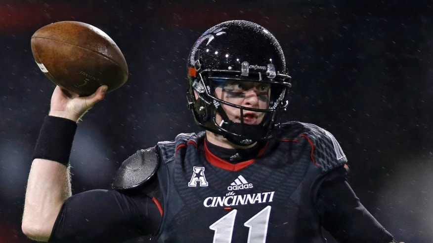 In the rain, Cincinnati quarterback Brendon Kay passes against Louisville in the first half of an NCAA college football game on Thursday, Dec. 5, 2013, in Cincinnati. (AP Photo/Al Behrman)
