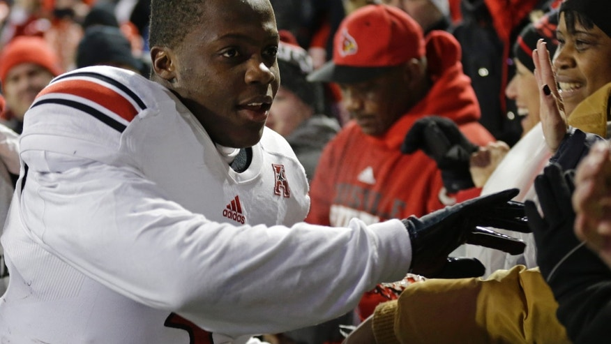 Louisville quarterback Teddy Bridgewater thanks the fans after defeating Cincinnati 31-24 in overtime in an NCAA college football game on Thursday, Dec. 5, 2013, in Cincinnati. (AP Photo/Al Behrman)