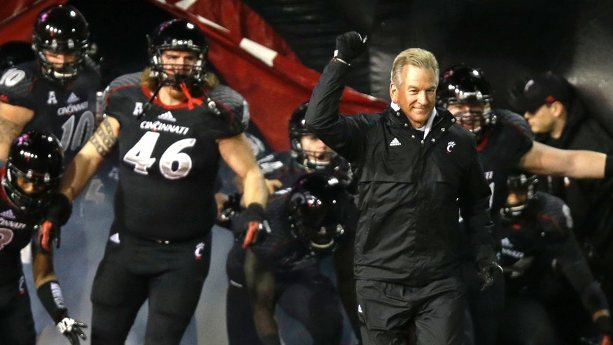 Cincinnati head coach Tommy Tuberville, right, leads his team onto the field at the start of an NCAA college football game against Louisville, Thursday, Dec. 5, 2013, in Cincinnati. (AP Photo/Al Behrman)