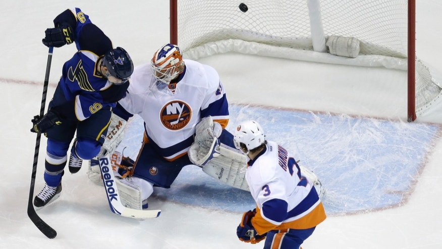 St. Louis Blues' Jaden Schwartz, left, watches as a shot by teammate Jay Bouwmeester slips past New York Islanders goalie Anders Nilsson, center, of Sweden, and Travis Hamonic, right, for a goal during the first period of an NHL hockey game Thursday, Dec. 5, 2013, in St. Louis. (AP Photo/Jeff Roberson)