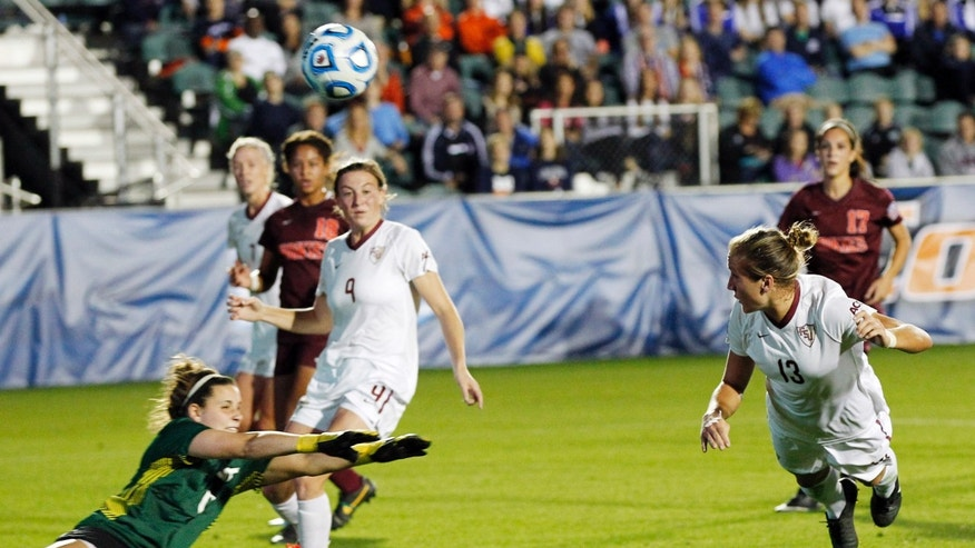 Florida State's Kristin Grubka (13) gets a header past Virginia Tech goaltender Dayle Colpitts, left, during the first half of an NCAA college soccer semifinal game at the Women's College Cup soccer tournament in Cary, N.C., Friday, Dec. 6, 2013. (AP Photo/Ellen Ozier)