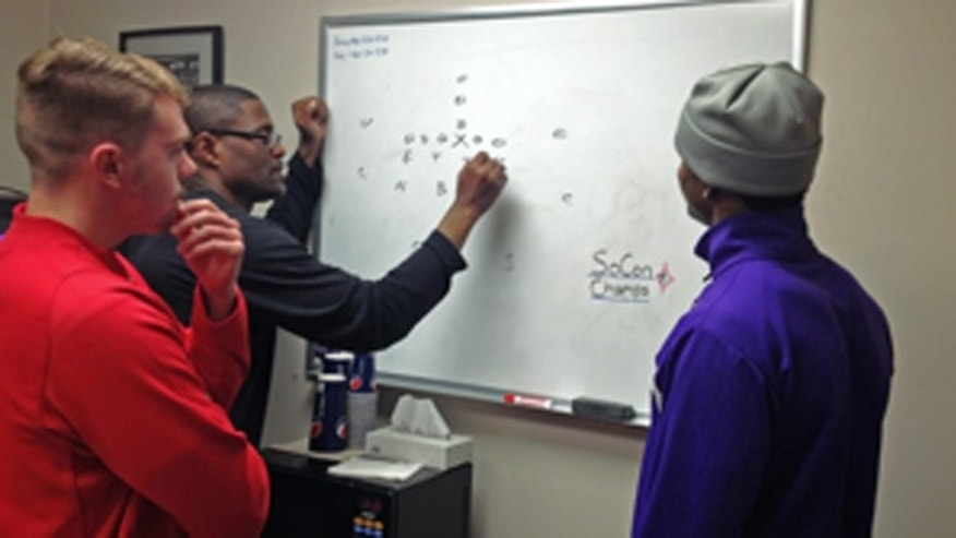 Furman University defensive back Jairus Hollman, right, and kicker Ray Early, left, look on in this undated photo as special teams coordinator Antonio Goss draws up a play.