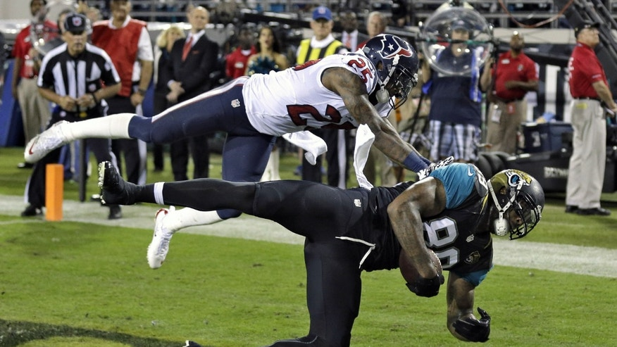 Jacksonville Jaguars tight end Marcedes Lewis (89) pulls in a one-yard touchdown reception in front of Houston Texans cornerback Kareem Jackson (25) during the first quarter of an NFL football game Thursday, Dec. 5, 2013, in Jacksonville, Fla. (AP Photo/Chris O'Meara)