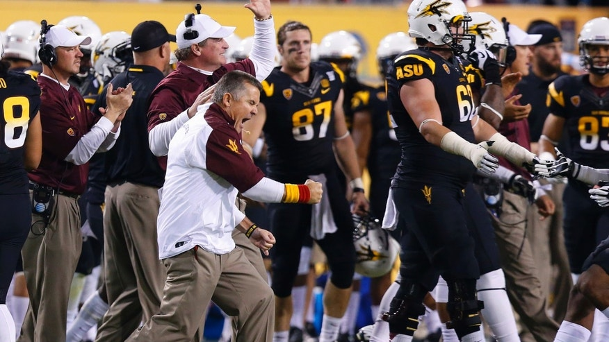 Arizona State coach Todd Graham, left,  pumps his fist as he celebrates a defensive stop against Arizona during the second half of an NCAA college football game Saturday, Nov. 30, 2013, in Tempe, Ariz. Arizona State defeated Arizona 58-21. (AP Photo/Ross D. Franklin)