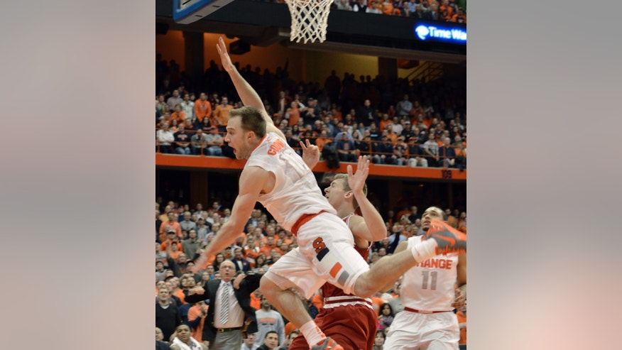 Syracuse's Trevor Cooney, left, sails out of control under the basket after being fouled by Indiana's Austin Etherington during the second half of an NCAA college basketball game in Syracuse, N.Y., Tuesday, Dec. 3, 2013. Etherington was ejected from the game. Syracuse won 69-52. (AP Photo/Kevin Rivoli)