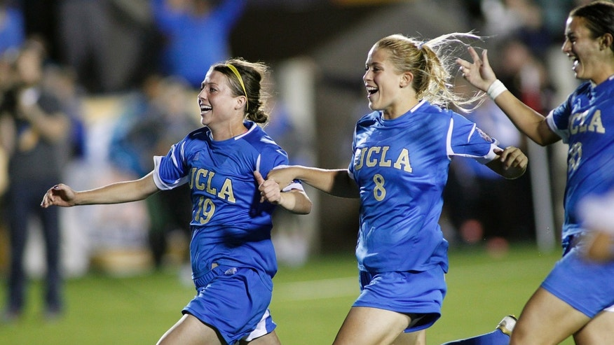 UCLA players, from left, Chelsea Stewart, Abby Dahlkemper and Kodi Lavrusky celebrate after UCLA beat Virginia in penalty kicks in an NCAA college soccer semifinal match at the Women's College Cup tournament in Cary, N.C., Friday, Dec. 6, 2013. (AP Photo/Ellen Ozier)