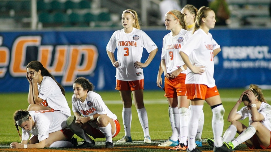 Virginia players react after losing in penalty kicks to UCLA in an NCAA soccer semifinal match at the Women's College Cup tournament in Cary, N.C., Friday, Dec. 6, 2013. (AP Photo/Ellen Ozier)