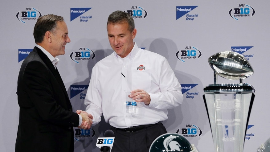 Michigan State head coach Mark Dantonio, left, shakes hands with Ohio State head coach Urban Meyer during a news conference for the Big Ten Conference championship NCAA college football game Friday, Dec. 6, 2013, in Indianapolis. Ohio State will play Michigan State, Saturday for the championship. (AP Photo/Darron Cummings)
