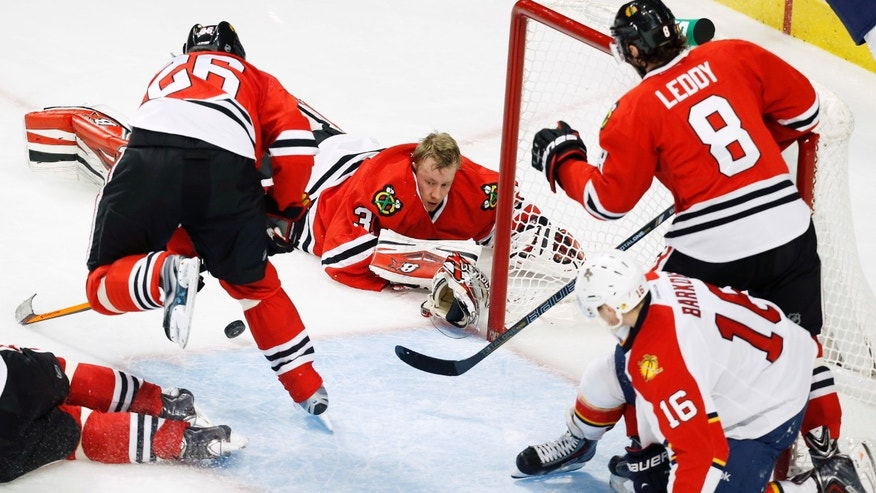Chicago Blackhawks goalie Antti Raanta (31) loses his helmet on a play during the third period of an NHL hockey game against the Florida Panthers on Sunday, Dec. 8, 2013, in Chicago, Ill. (AP Photo/Andrew A. Nelles)