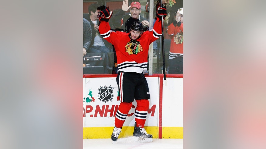 Chicago Blackhawks left wing Brandon Saad (20) celebrates scoring a goal against the Florida Panthers during the third period of an NHL hockey game on Sunday, Dec. 8, 2013, in Chicago, Ill. (AP Photo/Andrew A. Nelles)