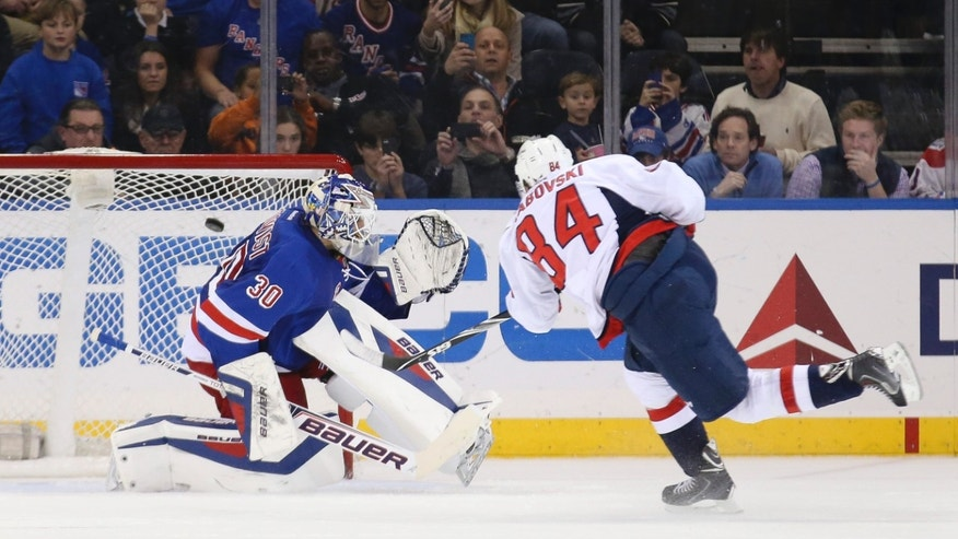 Washington Capitals center Mikhail Grabovski (84), of Germany, scores on New York Rangers goalie Henrik Lundqvist (30), of Sweden, on a penalty shot in the second period of an NHL hockey game on Sunday, Dec. 8, 2013, in New York. (AP Photo/John Minchillo)