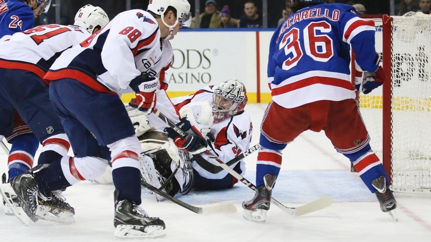 Washington Capitals goalie Philipp Grubauer (31), of Germany, makes a save as Steve Oleksy (61),  Nate Schmidt (88), and New York Rangers' Mats Zuccarello (36), of Norway, look on in the second period of an NHL hockey game on Sunday, Dec. 8, 2013, in New York. (AP Photo/John Minchillo)