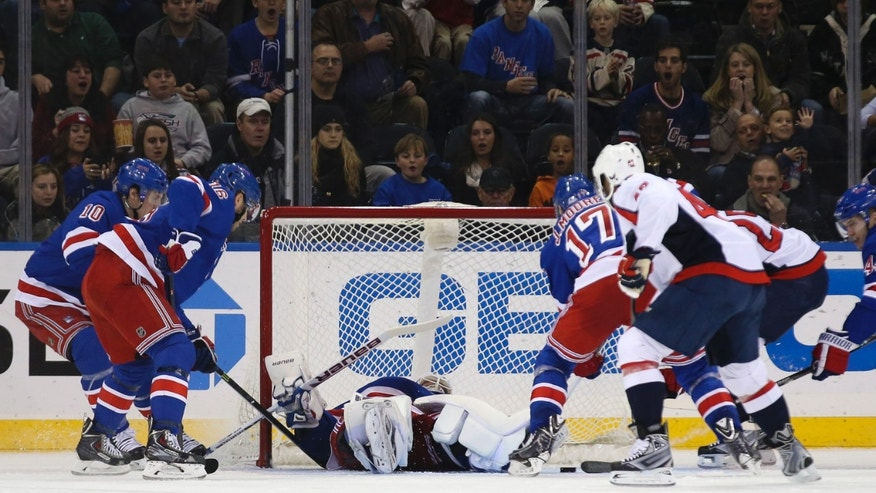 New York Rangers goalie Henrik Lundqvist (30), of Sweden, falls to his back as Washington Capitals left wing Jason Chimera (25), second from right, scores during the second period of an NHL hockey game on Sunday, Dec. 8, 2013, in New York. (AP Photo/John Minchillo)