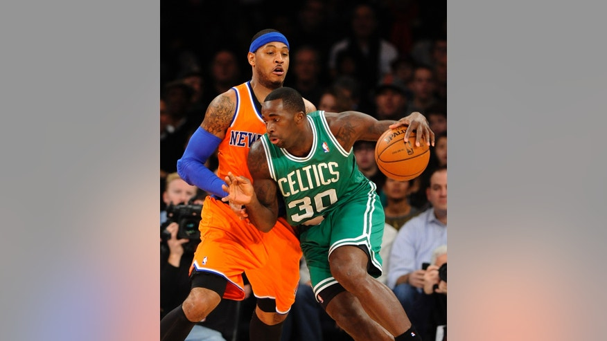 Boston Celtics power' Brandon Bass (30) drives the ball around New York Knicks Carmelo Anthony (7) in the first half an NBA basketball game on Sunday, Dec. 8, 2013, in New York. (AP Photo/Kathy Kmonicek)