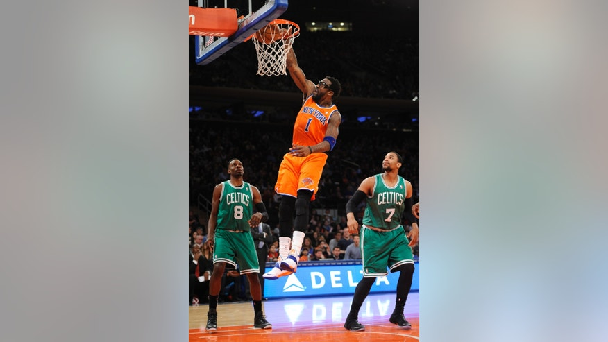 New York Knicks' Amar'e Stoudemire (1) shoots a basket between Boston Celtics' Jeff Green (8) and Jared Sullinger (7) during the first half an NBA basketball game on Sunday, Dec. 8, 2013, in New York. (AP Photo/Kathy Kmonicek)