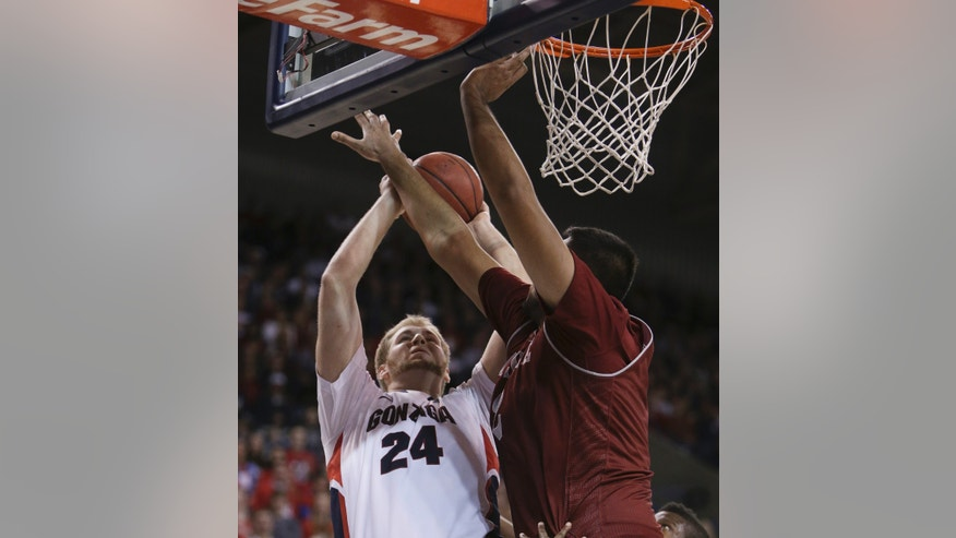 Gonzaga's Przemek Karnowski (24) attempts a jump shot against New Mexico State's Sim Bhullar during the first half of an NCAA basketball game, in Spokane, Wash., on Saturday, Dec. 7, 2013. (AP Photo/Young Kwak)