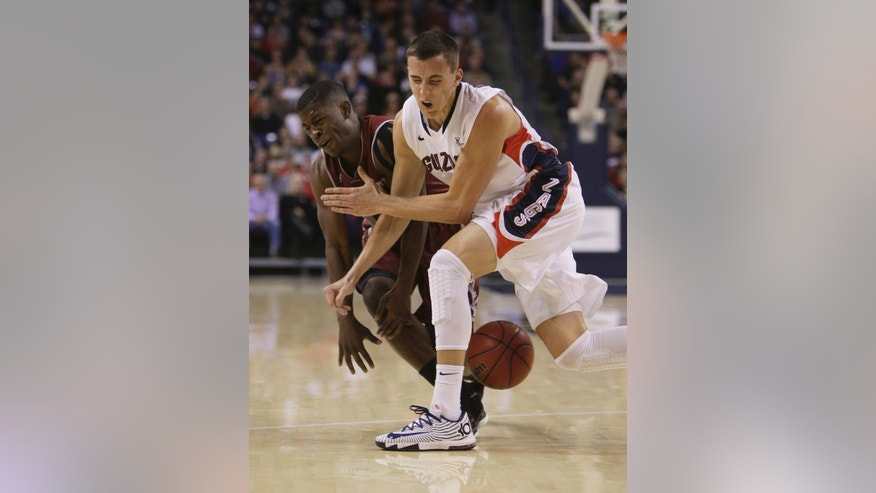 Gonzaga's Kyle Dranginis, right, and New Mexico State's K.C. Ross-Miller fight for a loose bll during the first half of an NCAA basketball game, in Spokane, Wash., on Saturday, Dec. 7, 2013. (AP Photo/Young Kwak)