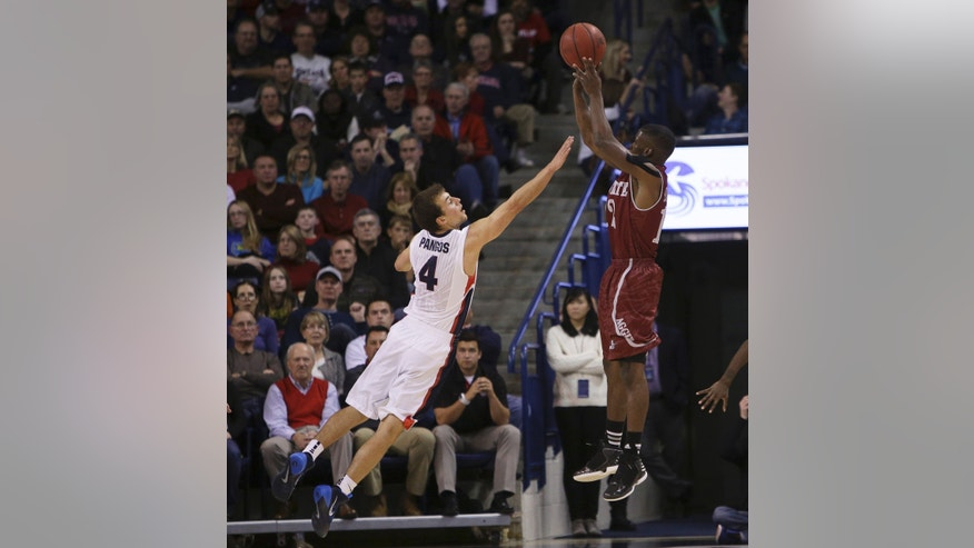 New Mexico State's K.C. Ross-Miller, right, attempts a jump shot against Gonzaga's Kevin Pangos during the first half of an NCAA basketball game, in Spokane, Wash., on Saturday, Dec. 7, 2013. (AP Photo/Young Kwak)