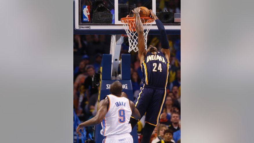 Indiana Pacers forward Paul George (24) dunks in front of Oklahoma City Thunder forward Serge Ibaka (9) in the first quarter of an NBA basketball game in Oklahoma City, Sunday, Dec. 8, 2013. (AP Photo/Sue Ogrocki)