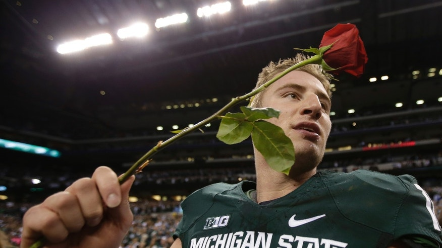 Michigan State's Connor Cook holds a rose after Michigan State defeated Ohio State, 34-24 in the Big Ten Conference championship NCAA college football game Saturday Dec. 7, 2013, in Indianapolis. (AP Photo/AJ Mast)