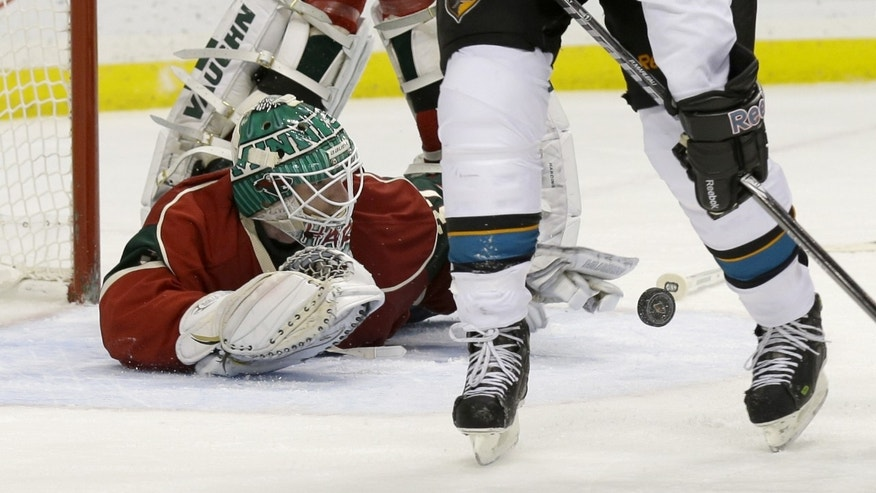 Minnesota Wild goalie Josh Harding dives to stop a shot by the San Jose Sharks during the second period of an NHL hockey game in St. Paul, Minn., Sunday, Dec. 8, 2013. (AP Photo/Ann Heisenfelt)