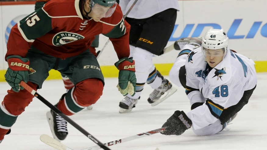 San Jose Sharks center Tomas Hertl (48), of the Czech Republic, dives for the puck as Minnesota Wild defenseman Jonas Brodin (25) beats him to it during the second period of an NHL hockey game in St. Paul, Minn., Sunday, Dec. 8, 2013. (AP Photo/Ann Heisenfelt)