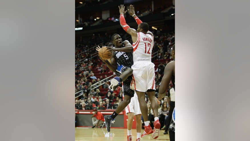 Orlando Magic shooting guard Victor Oladipo (5) drives to the basket on Houston Rockets power forward Dwight Howard (12) during the first quarter of an NBA basketball game on Sunday, Dec. 8, 2013, in Houston. (AP Photo/Bob Levey)