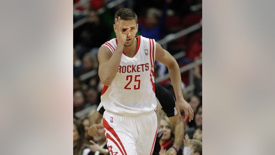 Houston Rockets small forward Chandler Parsons (25) signals after making a three-pointer against the Orlando Magic during the first quarter of an NBA basketball game on Sunday, Dec. 8, 2013, in Houston. (AP Photo/Bob Levey)