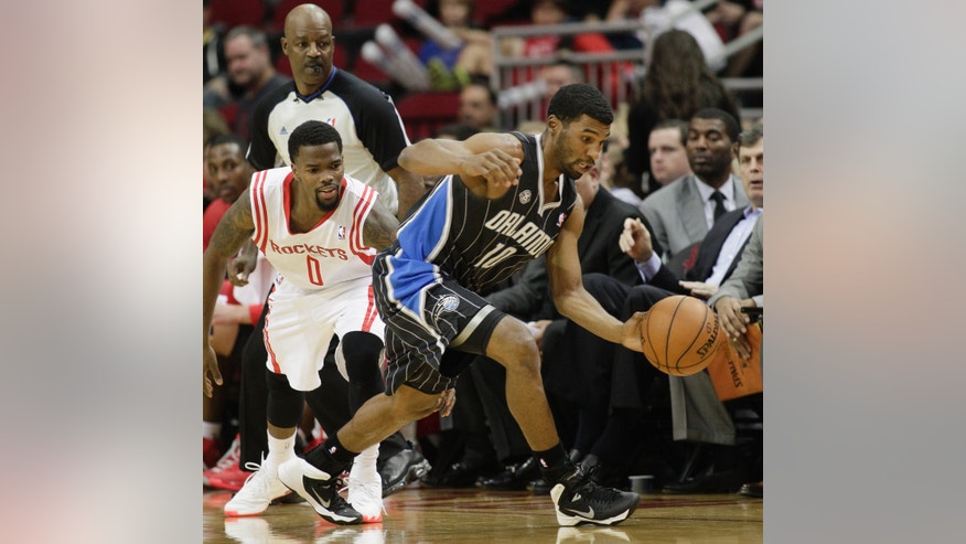 Orlando Magic point guard Ronnie Price (10) steals the ball from Houston Rockets point guard Aaron Brooks (0)during the first quarter of an NBA basketball game Sunday, Dec. 8, 2013, in Houston. (AP Photo/Bob Levey)