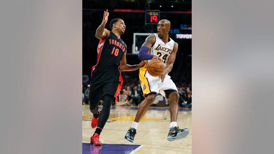 Los Angeles Lakers' Kobe Bryant, right, passes the ball around Toronto Raptors' DeMar DeRozan, left, during the first quarter of an NBA basketball game in Los Angeles, Sunday, Dec. 8, 2013. (AP Photo/Danny Moloshok)
