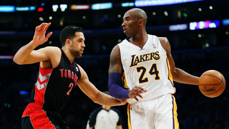 Los Angeles Lakers' Kobe Bryant dribbles the ball as he is guarded by Toronto Raptors' Landry Fields, left, during the first quarter of an NBA basketball game in Los Angeles, Sunday, Dec. 8, 2013. (AP Photo/Danny Moloshok)