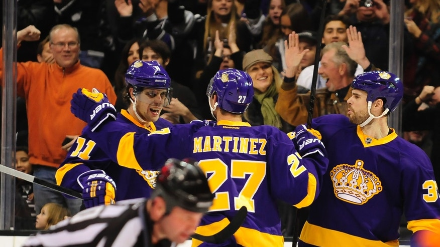 Los Angeles Kings defenseman Alec Martinez (27) and defenseman Willie Mitchell (33) celebrate teammate center Anze Kopitar, left, of Slovenia, goal during the second period of an NHL hockey game against the New York Islanders, Saturday, Dec. 7, 2013, in Los Angeles.(AP Photo/Gus Ruelas)
