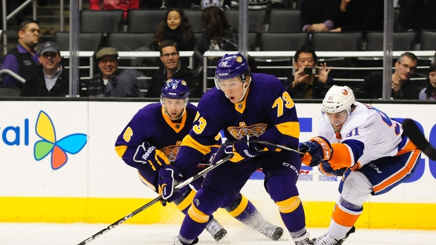 New York Islanders center John Tavares (91) reaches for Los Angeles Kings center Tyler Toffoli (73) as teammate defenseman Jake Muzzin (6) looks on as they battle for the puck during the second period of an NHL hockey game, Saturday, Dec. 7, 2013, in Los Angeles.(AP Photo/Gus Ruelas)