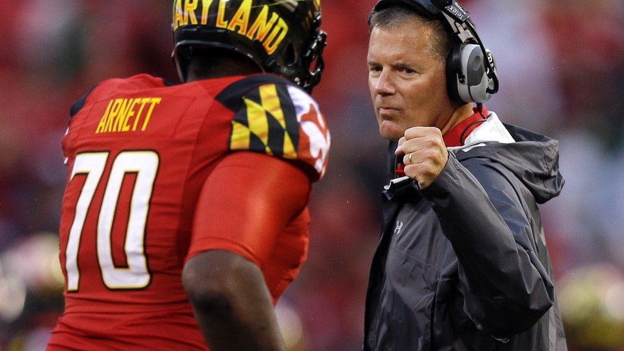 FILE - In this Sept. 21, 2013 file photo, Maryland head coach Randy Edsall fist bumps offensive linesman De'Onte Arnett as he jogs off the field during an NCAA college football game against West Virginia in Baltimore. Maryland won't have to cross the state line for its first bowl appearance since 2010. The Terrapins will face Marshall in the Military Bowl on Dec. 27. The game will be held at the home stadium of the Naval Academy, which is around 28 miles from the Maryland campus. (AP Photo/Patrick Semansky, File)