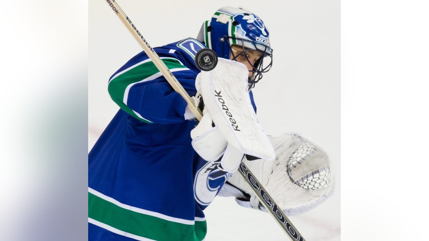 Vancouver Canucks' goalie Roberto Luongo makes a blocker save against the Colorado Avalanche during second period NHL hockey game in Vancouver, British Columbia on Sunday, Dec. 8, 2013. (AP Photo/The Canadian Press, Darryl Dyck)