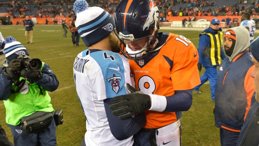 Denver Broncos quarterback Peyton Manning (18) and Tennessee Titans quarterback Ryan Fitzpatrick (4) talks following an NFL football game on Sunday, Dec. 8, 2013, in Denver. (AP Photo/Jack Dempsey)